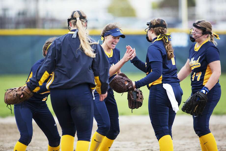 Midland High School's girls softball infield players deliberate at the pitcher mound before playing in a game against Bay City Central High School at Midland High School on Thursday. Photo: Theophil Syslo