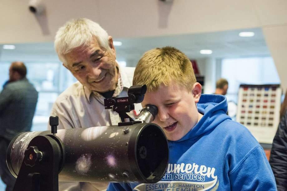 """Sunset Astronomical Society member James Whang watches as Hayden Gallegos, 9, of Essexville looks through a telescope aimed at signs outside the planetarium during a National Astronomy Day event at the Delta College Planetarium on Saturday, April 29.  """"That's so cool!"""" Hayden exclaimed as he looked. He said that he had an astronomy book from school and was learning about the subject. Photo: Danielle McGrew Tenbusch"""