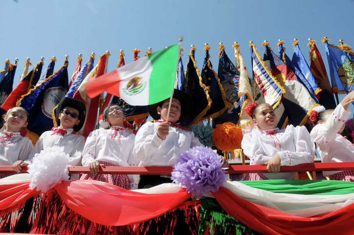Children in costume wave flags aboard the E.A. Squatty Lyons float in the 21st Annual LULAC Cinco de Mayo Parade downtown Saturday  May 7,2016(Dave Rossman Photo)