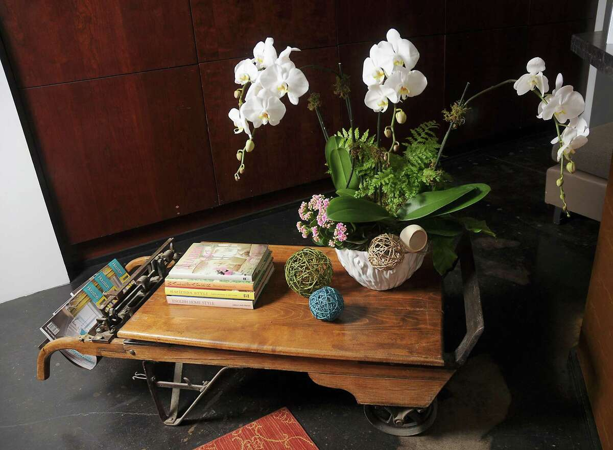 Adrian Laday and Sharon Staley at ASID Texas Gulf Coast Chapter: An old cotton bale scale serves as a unique base for a stack of books, a luscious display of orchids with greenery and balls made of natural fiber.