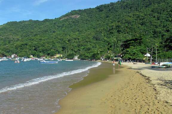 In this Feb. 13, 2017 photo, tourists walk along the beach in the small village Vilo do Abraao in Ilha Grande, or Big Island, about three hours from Rio de Janeiro. The tropical island remains pristine in large because of an unusual history that includes being a pirate refuge, leper colony and site of a major prison. Still, there are worries about the future as its focus goes from fishing to tourism. (AP Photo/Peter Prengaman) ORG XMIT: NYLS403