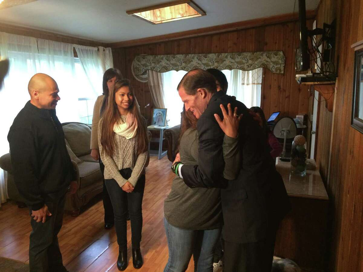 U.S. Sen. Richard Blumenthal is hugged by Dora Barrios during the Senator's visit to the couple's home in Derby Friday. The story of Dora's husband, Luis's impending deportation has captured nationwide interest.