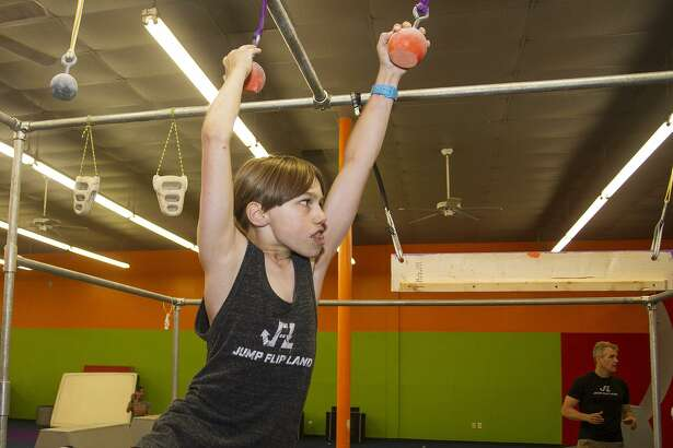 Tanner Haschke, 11, negotiates the cannonball alley obstacle at Jump, Flip, Land, a new gym that teaches kids ninja warrior-type skills.