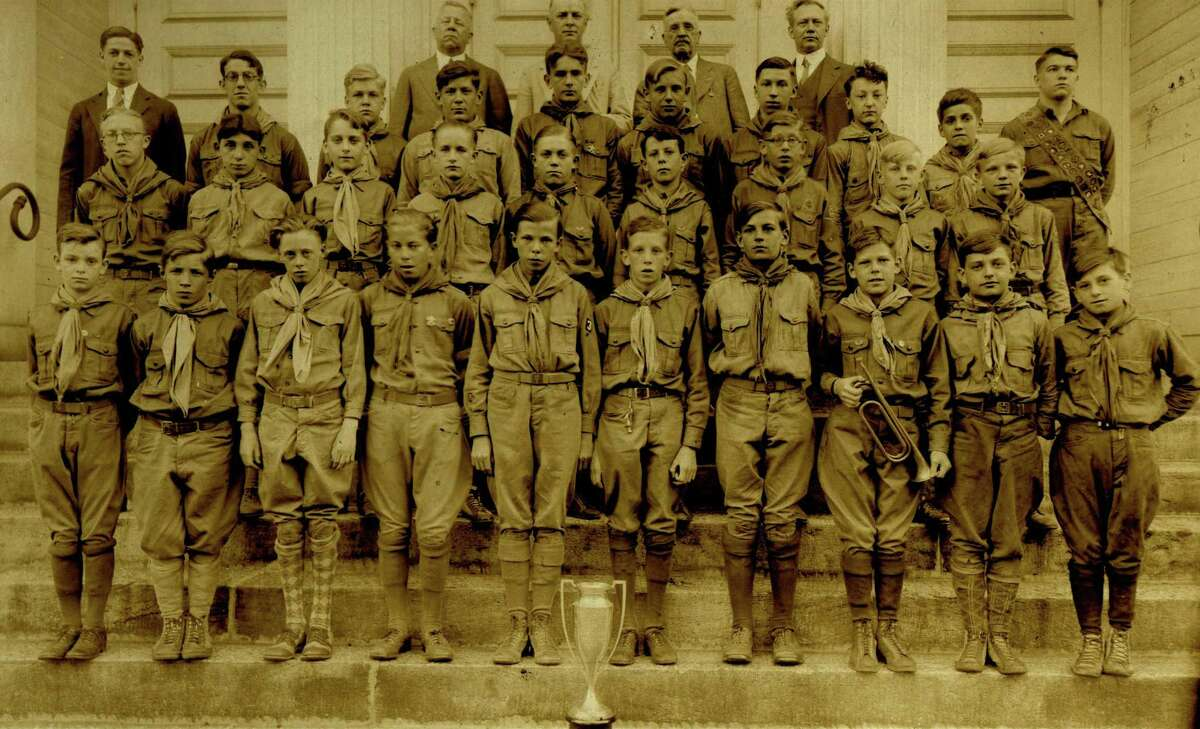This is a picture of the 1929 troop on the steps of the Derby 2nd Congregational Church when Troop 3 won the Presidents Cup from the Housatonic Council Boy Scouts of America. James O'Sullivan believes he is in the picture third row from the top, third scout from the right with glasses. The person in the far right back row is Edmund D. Strang. He along with the two people in the far left (far left Manuel Pearson and next to him in glasses is Francis Barron) founded Cub Scout Pack 3 in 1927. The Boy Scout Troop 3 Scoutmaster at the time was Reverand Alfred Budd, he is in the suit in the back row, to the left of Ed Strang. Rev. Budd was the minister of the Derby 2nd Congregational Church, sponsoring organization of Troop 3. The president's cup was manufactured by the Derby Silver Company and presented by Housatonic Council President to the scout troop in the Lower Naugatuck Valley with the most rank advancements for the year. Troop 3 won it in both 1928 and 1929, the only years the cup was offered.