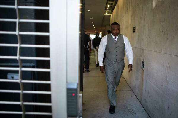 Community activist Quanell X walks out of the Houston Police Department headquarters after accompanying murder suspect Jeffery C. Archangel, 25, who was charged Thursday with killing Javier Flores, so Archangel could turn himself in, Friday, May 5, 2017, in Houston.