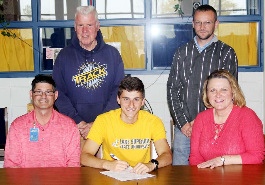 Kendal Delpiere signed with Lake Superior State University to run cross country and track. Front, from left, Delpiere is pictured with parents Brian Delpiere and Kim Delpiere. Back, from left, coaches Lee Kahler and Nick Rochefort.