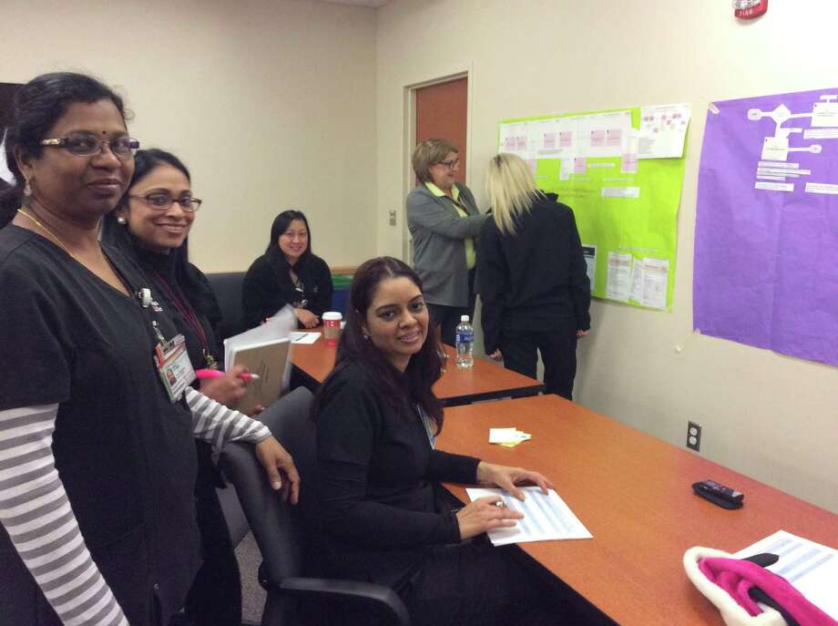 Harjeet Kaur, clinical nurse leader (seated front); Anitha Madhu, clinical charge nurse (left); Tessy Siby, clinical nurse leader; Phuong Tran (seated, no longer at MD Anderson); and Colleen Hughes, registered nurse (back to camera), prioritize steps to enhance standard of care for patient responsivity with Laurie Kaufman, manager of clinical quality improvement.