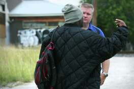 San Antonio police officer Monty McCann talks with Bryant Crawford near his camp along I-10 at Culebra. McCann and fellow officer Joe Farris Jr. are the creators of the Hope Team, Homeless Outreach Positive Encounters, helping those living on the streets regain their identification information and with housing.