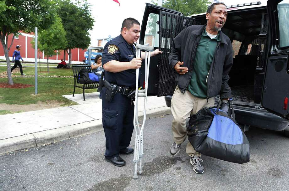 After talking with McCann and Farris, Bruce Givens hobbles out of a police wagon as officer Arthur Lopez holds the door at Haven for Hope Photo: Bob Owen /San Antonio Express-News / ©2017 San Antonio Express-News