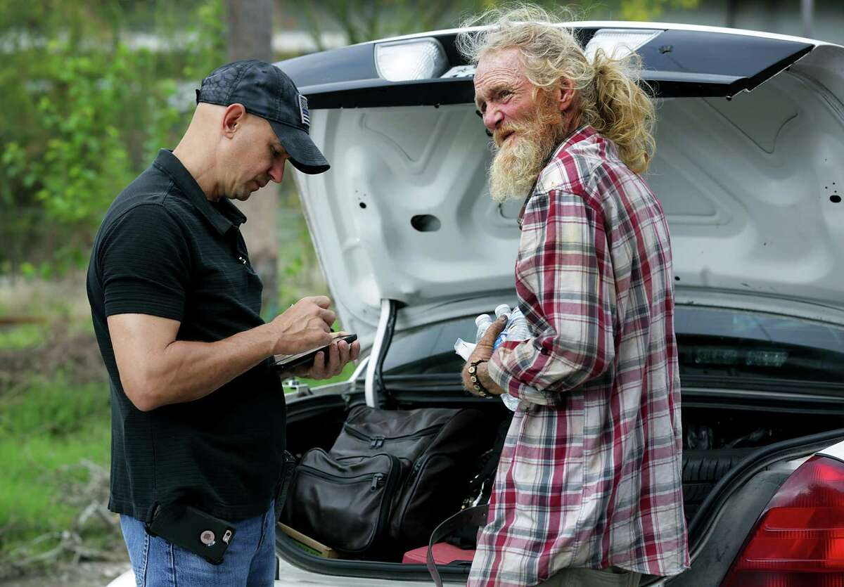 In this 2017 photo, a San Antonio police officer helps a homeless man. As we re-think how we respond to mental health crises, police will stay play a role, and often partner with mental health professionals.