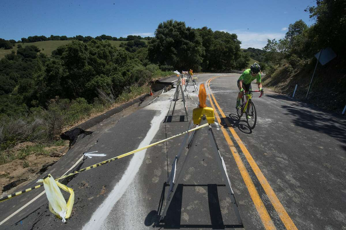 A professional cyclist rides along damaged Redwood Road in Castro Valley.