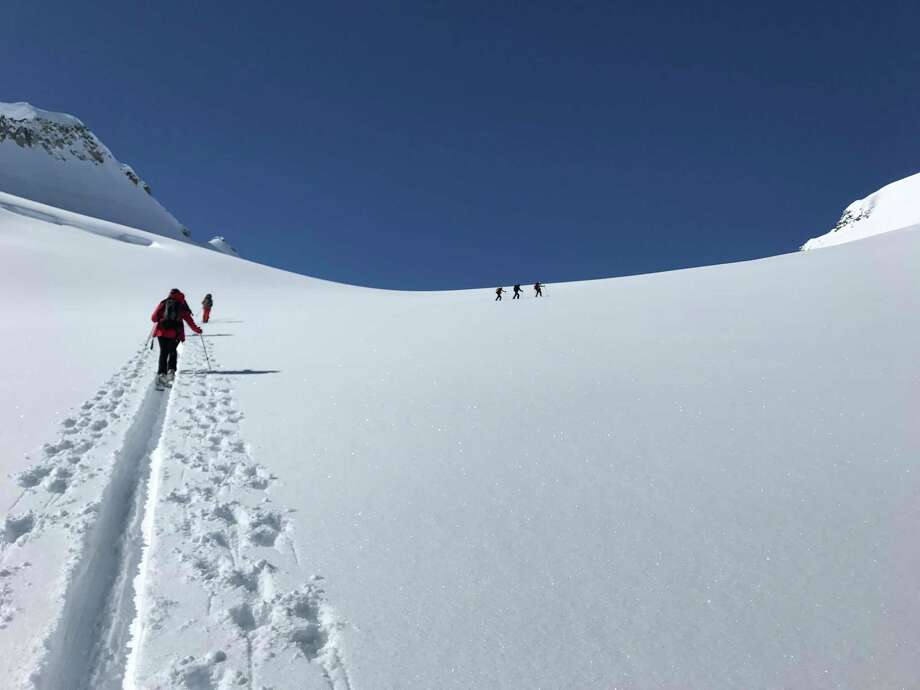 """A group of back country skiers works its way up a slope on an """"up-track,"""" or path up to the summit, in the Purcell Mountains in British Columbia. Photo: Ryan Maye Handy"""