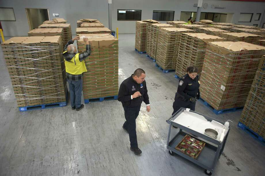 A U.S. Customs and Border Protection (CBP) officer, right, and a Servicio de Administracion Tributaria (SAT) officer, center, prepare to inspect Driscoll Strawberry Associates Inc. brand strawberries during an agricultural inspection at the CBP-SAT Pre-inspection Pilot Facility in Tijuana, Mexico, on Wednesday, Jan. 18, 2017. The conflict over the border wall and trade adds to tensions in the U.S.-Mexico relationship, the outcome of which has domestic political implications and economic consequences in both countries. Photographer: David Maung/Bloomberg Photo: David Maung, Bloomberg / © 2017 Bloomberg Finance LP