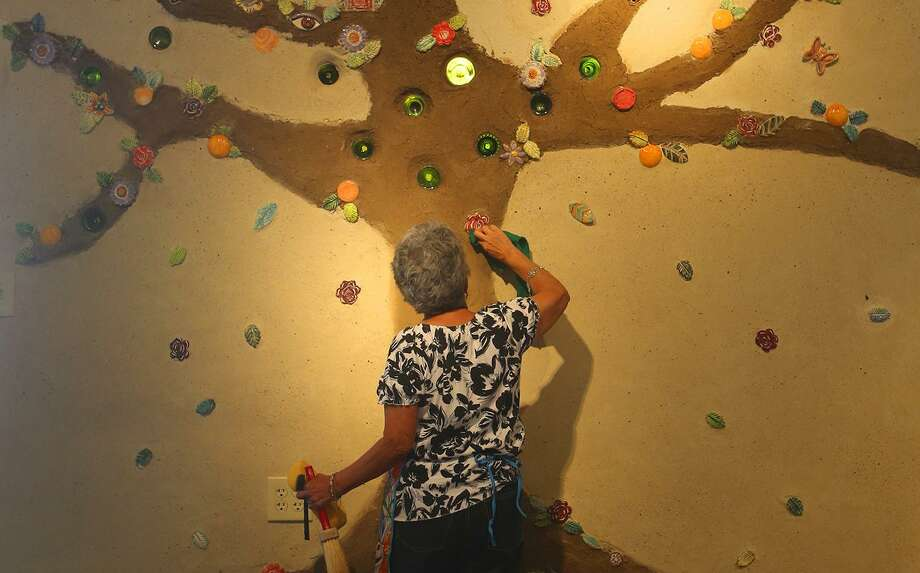 Olga Martinez, a member of MujerArtes, cleans new art work, part of a tree of life at MujerArtes' new building on South Colorado Street. The new building will house the clay arts cooperative studio. Photo: John Davenport /San Antonio Express-News / ©San Antonio Express-News/John Davenport
