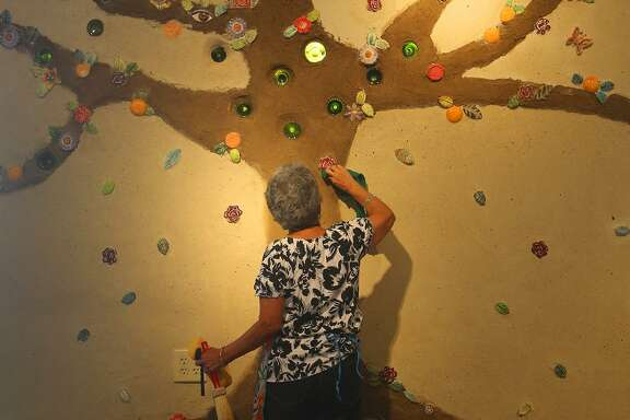 Olga Martinez, a member of MujerArtes, cleans new art work, part of a tree of life at MujerArtes' new building on South Colorado Street. The new building will house the clay arts cooperative studio.