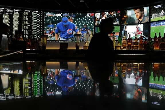 A screen showing a Chicago Cubs spring training baseball game is reflected with other screens on a countertop at the Westgate Superbook sports book, Friday, March 31, 2017, in Las Vegas. Oddsmakers in Las Vegas predict the Chicago Cubs will successfully defend their World Series title in 2017. The city's sports books like the team to win it all, with the biggest ones making them a 7-2 favorite to win it all again.(AP Photo/John Locher)
