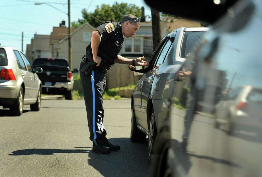 Danbury Police Officer Ricard DeJesus stops a car on West Street in Danbury, after observing the driver using a mobile devise. Photo: Carol Kaliff / File Photo / The News-Times