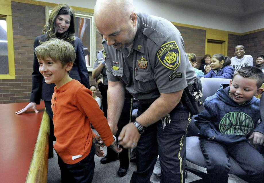 Sgt. John Pavia handcuffs Stavros Kallianiotis, 8, to take him into custody at the state Superior Court in Danbury on Friday. Stavros was visiting the court with other third-graders from King Street Primary School in Danbury for the court's Law Day celebration. Left is Attorney Wendy Grispin, the day's co-ordinator. Photo: Carol Kaliff / Hearst Connecticut Media / The News-Times