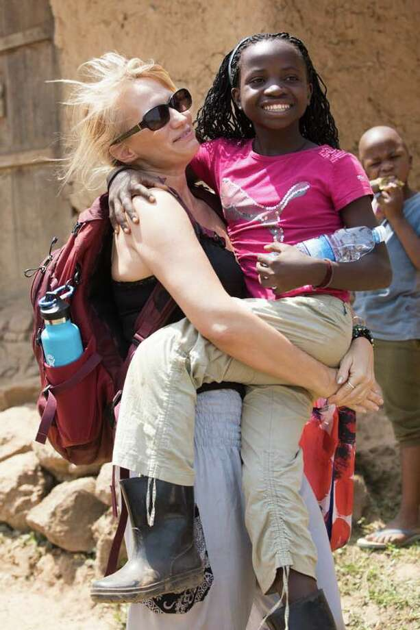 Former Atascocita resident Wendee Nicole carries Joyce, an 11-year-old Batwa girl Wendee Nicole has adopted from Uganda. Wendee Nicole sold her house and moved to Uganda to help the children there in 2014. Photo: David Barron