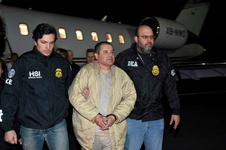 "FILE - In this Jan. 19, 2017 file photo provided by U.S. law enforcement, authorities escort Joaquin ""El Chapo"" Guzman, center, from a plane to a waiting caravan of SUVs at Long Island MacArthur Airport, in Ronkonkoma, N.Y. U.S. District Judge Brian Cogan ruled Thursday, May 4, 2017, that Guzman needs to stay in solitary confinement at a New York City lockup to keep him from trying to control his drug-trafficking empire from behind bars. Cogan rejected a request by Guzman's defense team to order him released from an ultrahigh-security wing of a jail in lower Manhattan and be allowed in the general inmate population and receive visitors. (U.S. law enforcement via AP, File) ORG XMIT: NYSP102 / U.S. law enforcement"