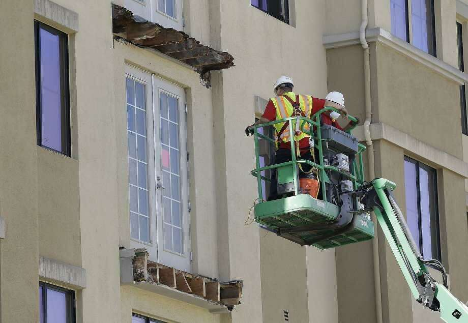 A crew works on the remaining wood of an apartment building balcony that collapsed, top, and one that was removed, below, in Berkeley, Calif., Thursday, June 18, 2015. A balcony broke loose from an apartment building during a 21st birthday party, killing several and seriously injuring several others. Photo: Associated Press / Jeff Chiu