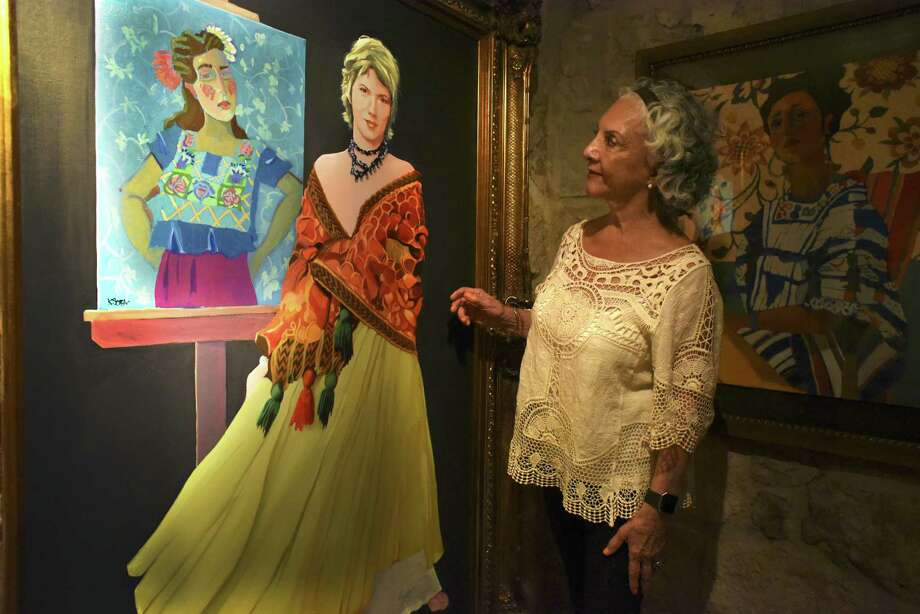 Velma Villegas, retired superintendent of the Southwest Independent School District, admires a painting of Kathy Sosa done by Lionel Sosa on Thursday, May, 4, 2017.  The Sosas opened their gallery as part of the Big Give event. They offered to donate half of all proceeds from paintings sold during the event to KIPP Academy, a charter school in San Antonio. The Big Give is a 24-hour day of giving to local charities and nonprofits. Photo: Billy Calzada, Staff / San Antonio Express-News / San Antonio Express-News