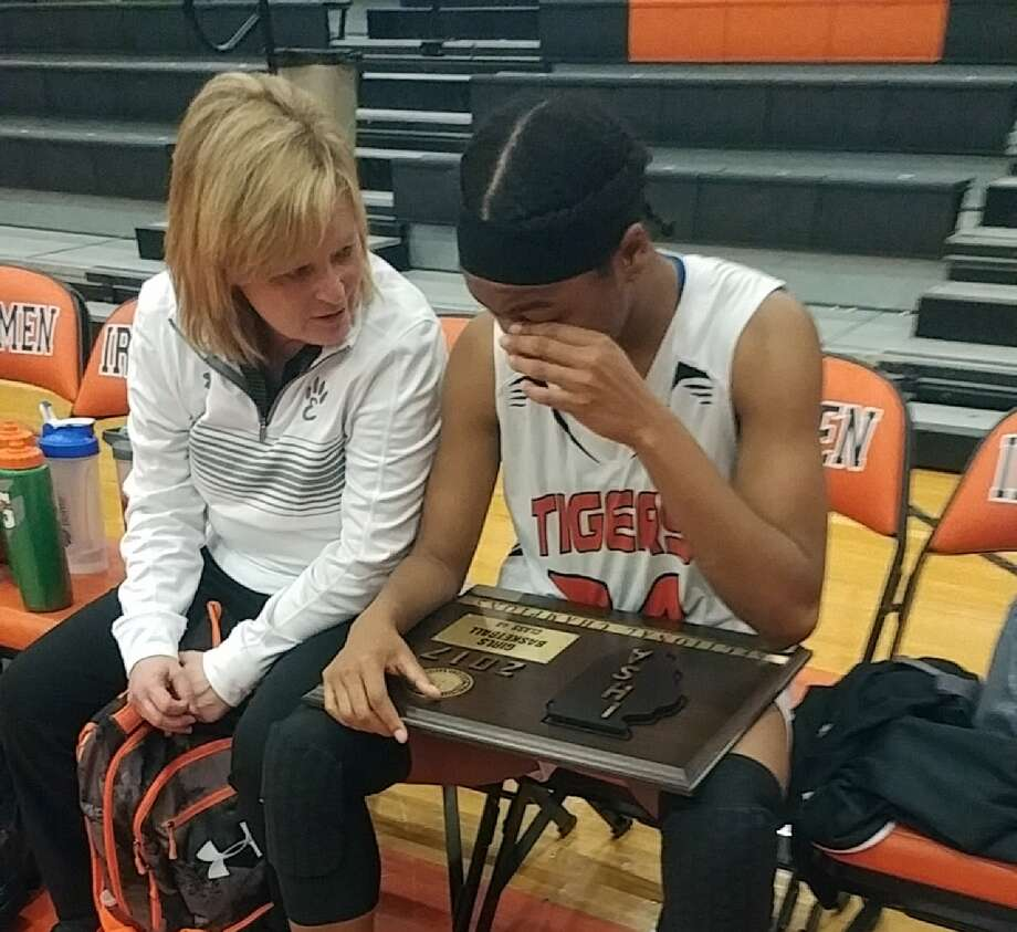Edwardsville girls' basketball assistant coach Donna Farley, left, talks to junior forward Myriah Noodel-Haywood after the Tigers won the Class 4A Normal Community Sectional championship.