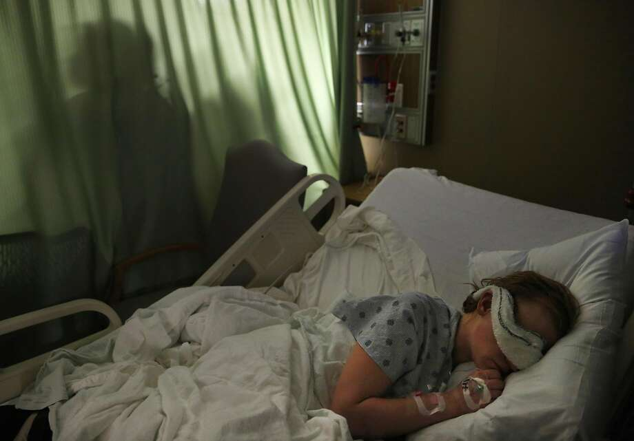 """Ashley Hensley, 24, tries to sleep as a family loudly visits her roommate in her hospital room April 14, 2017 in Modesto, Calif. Hensley says she has severe social anxiety related to crowds, which she attributes to her multiple months-long experiences in juvenile hall as an adolescent. Hensley was found in a park, nearly dead in a coma after she did crystal meth and her blood sugar levels spiked to dangerous levels due to her untreated type-I diabetes. Hensley said she was tired of being a drug addict and though she was in the hospital, 24 was the best birthday she has had in a few years. Hensley is currently homeless, using crystal meth. Hensley alleges she only tried the drug after her son's father took their baby with no notice and fled the state a few years ago, sending Hensley into deep despair. Hensley was removed from her abusive home life at the age of 9, separated from her siblings and had 32 different placements in foster care, including eight stops at Mary Graham Children's Shelter. During her time at Mary Graham, Hensley was sent to the San Joaquin County juvenile detention center four times, each stay lasting days to weeks at a time. Hensley, who was sexually abused as a child and raped multiple times as an adolescent says that the time in juvenile detention made her """"more angry"""" and has caused her to suffer from social anxiety as an adult. Photo: Leah Millis, The Chronicle"""