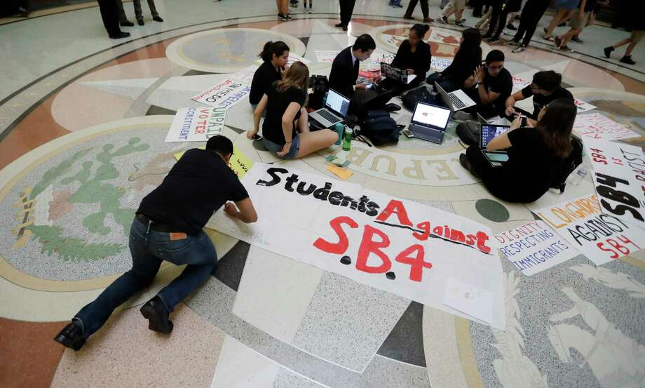 "Students gather in the Rotunda at the Texas Capitol to oppose SB4, an anti-""sanctuary cities"" bill that already cleared the Texas Senate and seeks to jail sheriffs and other officials who refuse to help enforce federal immigration law, as the Texas House prepares to debate the bill, Wednesday, April 26, 2017, in Austin, Texas.  Many sheriffs and police chiefs in heavily Democratic areas warn that it will make their jobs harder if immigrant communities, including crime victims and witnesses,  become afraid of police.  (AP Photo/Eric Gay) Photo: Eric Gay, STF / Copyright 2017 The Associated Press. All rights reserved."