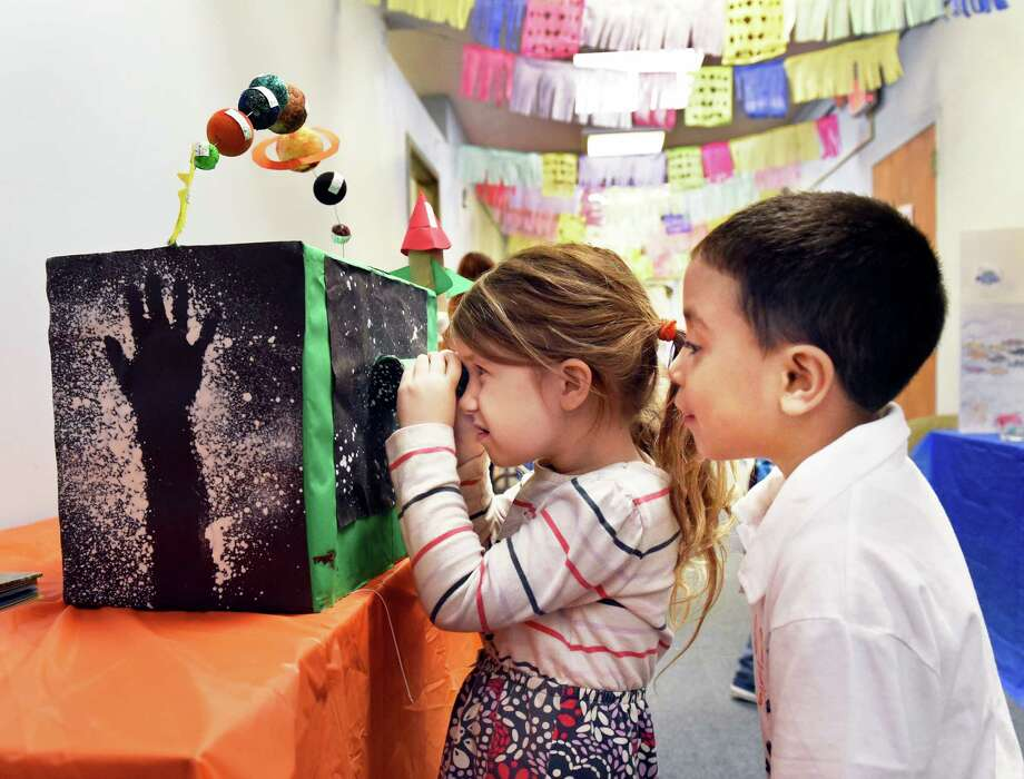 Five-year-old Svetlana Grover, left, takes a look through classmate Bryan Arroyo's planatarium poject during Castle Island Bilingual Montesso school's Feria De Espanol Friday May 5, 2017 in Albany, NY.  (John Carl D'Annibale / Times Union) Photo: John Carl D'Annibale / 20040434A