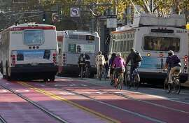 Buses and bicycles vie for space on Market Street near Fifth Street in San Francisco, Calif. on Wednesday, Oct. 21, 2015.