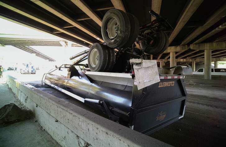 Authorities said the load of a dump truck was raised when the vehicle attempted to travel under a bridge in north Houston Friday.