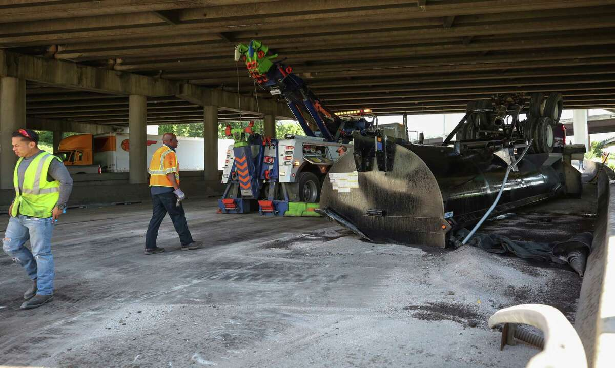 Authorities investigate the scene where a dump truck northbound on the Eastex Freeway struck an overpass at Loop 610, sending pieces of the truck flying. No one was seriously injured.
