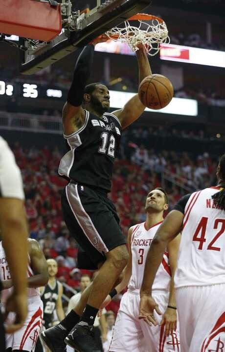 The Spurs' LaMarcus Aldridge (12) dunks against the Rockets at the Toyota Center on Friday. Aldridge tied Kawhi Leonard with a team-high 26 points. Photo: Kin Man Hui /San Antonio Express-News / ©2017 San Antonio Express-News