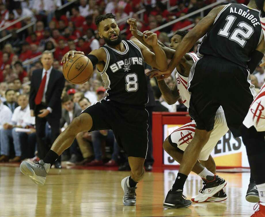 Spurs' Patty Mills (08) struggles to get away from Houston Rockets' Lou Williams (12) in Game 3 at the Toyota Center on Friday, May 5, 2017. Spurs defeated the Rockets, 103-92. (Kin Man Hui/San Antonio Express-News) Photo: Kin Man Hui, Staff / San Antonio Express-News / ©2017 San Antonio Express-News