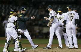 Oakland Athletics pitcher Andrew Triggs (60) hands the ball to manager Bob Melvin as he leaves in the sixth inning of a baseball game against the Detroit Tigers Friday, May 5, 2017, in Oakland, Calif. (AP Photo/Ben Margot)