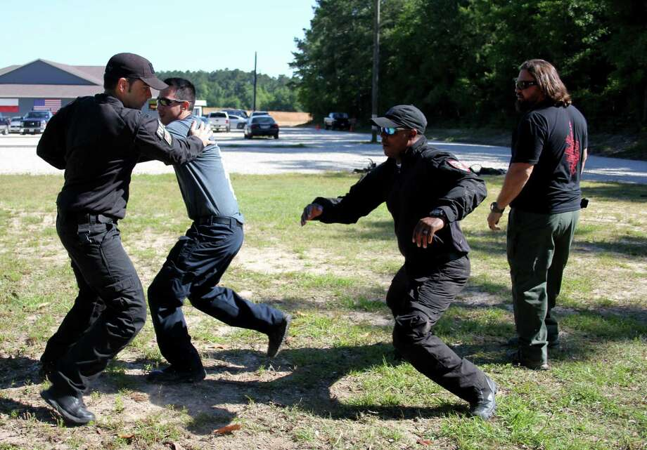 With instructor Michael Rodriguez standing nearby, officers Carlos Herrera, Chris Kerr and Scott Pierman go through hand-to-hand combat drills on Friday at Trinity Armory in Cleveland. The training was part of a six-day course offered by Houston-based AWATT to help police departments in Splendora, Patton Village, Roman Forest and Woodbranch form a joint special response team. Photo: Vanesa Brashier