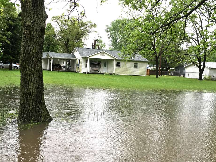 With rain falling Thursday, water rises in a front yard in Mitchell. Photo: Steve Horrell • Intelligencer