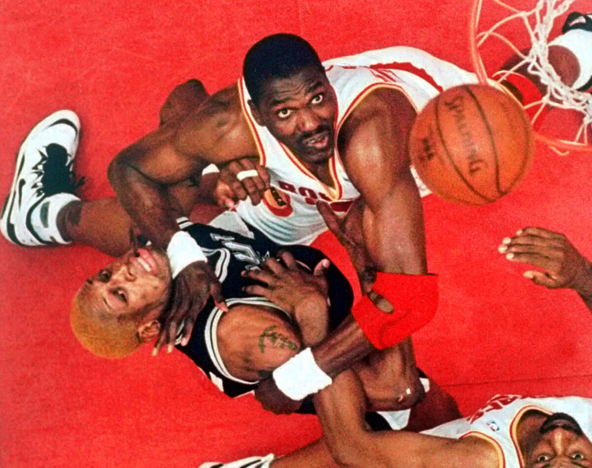 San Antonio Spurs forward Dennis Rodman, left, and Houston Rockets center Hakeem Olajuwon, top center, battle for a rebound as Houston's Charles Jones looks on at bottom right in the second quarter of their NBA Western Conference Finals game Sunday, May 28, 1995, in Houston. The final days are counting down on Hakeem Olajuwon's Houston Rockets contract, making him a free agent and possibly ending his brilliant 17-year Hall of Fame career. (AP Photo/Tim Johnson, File)