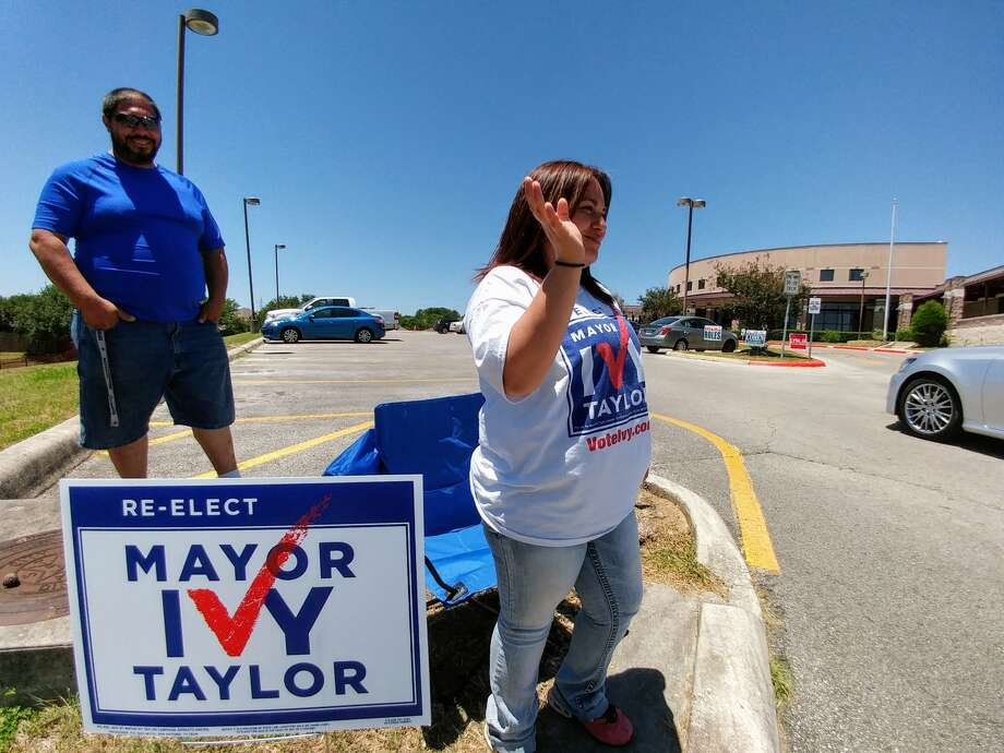 Campaign volunteer Jamie Rosas waves to voters outside Huebner Elementary School on Election Day, May 6, 2017. Photo: John Tedesco, Express-News