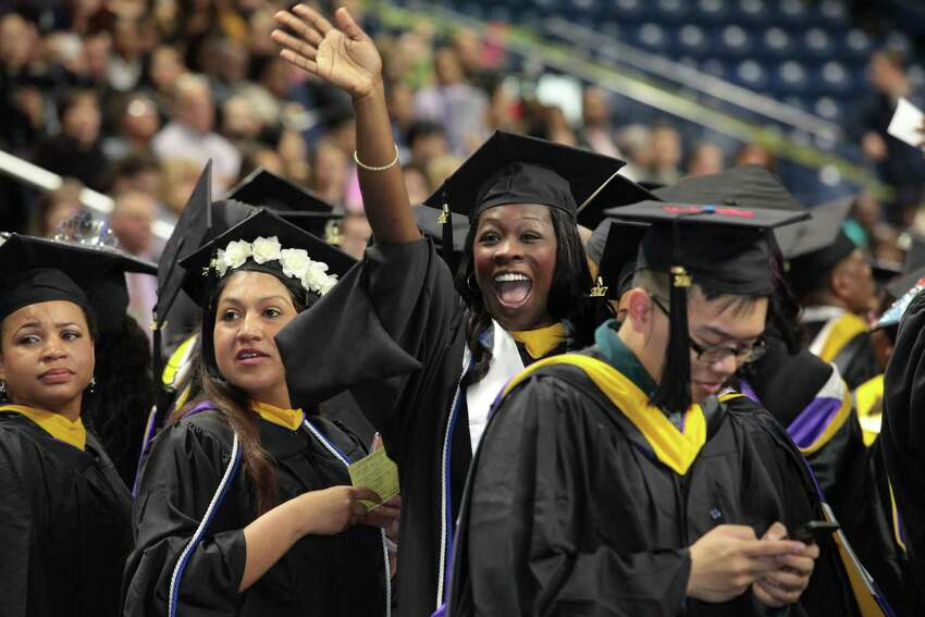 Cassandra Charles-Tabacco, of Stratford, waves to her husband and child at the University of Bridgeport commencement exercises at the Webster Arena in Bridgeport, Conn. on Saturday, May 6, 2017.
