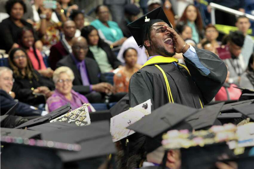 Above, Max Altidor, of Brooklyn, N.Y., leads a cheer during the University of Bridgeport commencement exercises at the Webster Arena on Saturday.