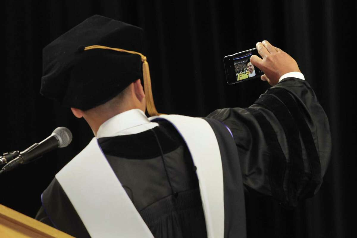 Ramon Peralta, Jr., honorary degree recipient and commencement speaker, takes a selfie before addressing the graduates at the University of Bridgeport commencement exercises at the Webster Arena in Bridgeport, Conn. on Saturday, May 6, 2017.
