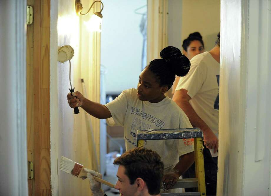 Kori Humphrey, the daughter of homeowner Jennifer Humphrey, works alongside volunteers painting a hallway in the family's Stamford home during the 30th annual HomeFront Day on Saturday. Approximately 30 volunteers pitched in to paint, repair plumbing, install new lighting, ceiling fans and smoke/carbon monoxide detectors and renovate the kitchen with new cabinets, counter tops and appliances. HomeFront is a community-based program dedicated to providing quality of life improvements to families with financial hardships. Since 1988, HomeFront volunteers have repaired over 3,000 homes, injecting nealy $50 million of assistance where it is needed most. Photo: Matthew Brown / Hearst Connecticut Media / Stamford Advocate