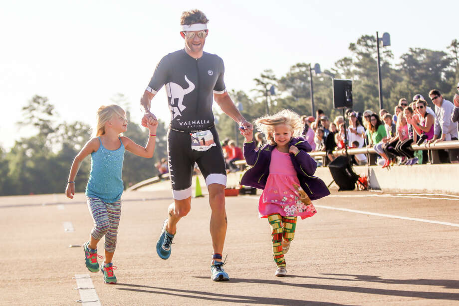 Triathlete Lars Finager approaches the finish line in first place, joined by his daughters Kaia, 6, and Elin, 3, during the CB&I TRI - The Woodlands Triathlon on Saturday, May 6, 2017, at Northshore Park. Photo: Michael Minasi/Houston Chronicle