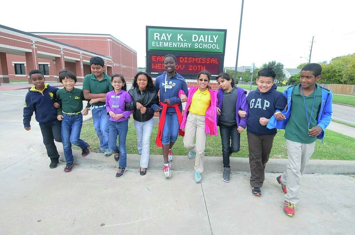 Fifth grade students from Daily Elementary pose for photos in front of their school Wednesday 11/20/13. L-R: Adrien Muhabuki (cq) (home language is Swahili) Soi Otani (cq) (home language is Japanese) Vivek Kuppili (cq) (home language is Telegu - India) Siddhi Rohit (cq) (home language is Gujarati - India) Alondra Duvernay (cq) (home language is English) Norya Traore (cq) (home language is French) Venkata Mannava (cq) (home language is Telegu - India) Sweety Tiwari (cq) (home language is Hindi) Pierre Duong (cq) (home language is Vietnamese) and Sami Bin Silm (cq) (home language is Arabic).