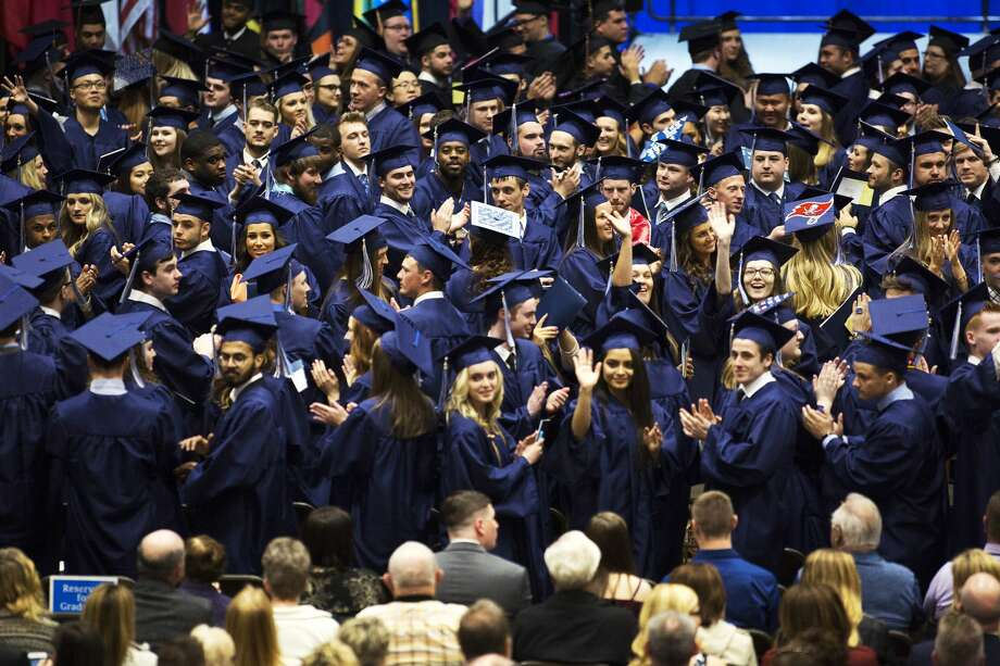 Northwood University students wave to their parents in a gesture of thanks during commencement on Saturday. Photo: Theophil Syslo