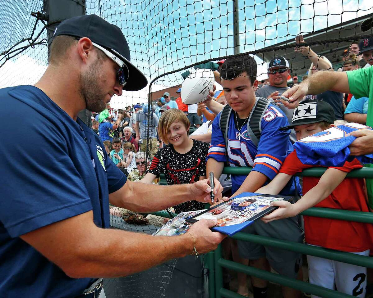 In this April 30, 2017 photo, Columbia Fireflies' Tim Tebow accommodates some lucky fans with an autograph before a minor league baseball game against the Hickory Crawdads at L.P. Frans Stadium in Hickory, N.C. The Single A teams of the South Atlantic League are seeing a burst in attendance whenever Tebow and the Columbia Fireflies go on the road. (Ernie Masche/Record/The Hickory Daily Record via AP) ORG XMIT: NCHIC201