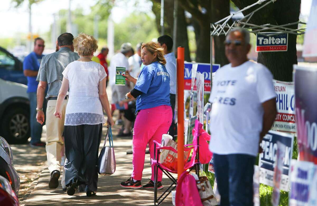Early voters pass candidate signs in front of the Pasadena City Hall on Tuesday. Isbell was term-limited from running for re-election.