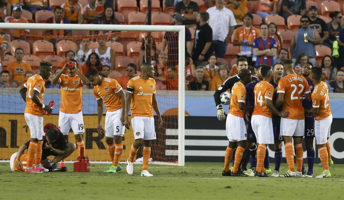 Orlando City SC forward Will Johnson (8) and Houston Dynamo defender Leonardo (22) become verbal at each other while Houston Dynamo forward Alberth Elis (17) is being checked by medic on the ground during the first half of the game at BBVA Compass Stadium Saturday, May 6, 2017, in Houston. Elis had collided with Orlando City SC goalkeeper Joseph Bendik (1) moments ago. ( Yi-Chin Lee / Houston Chronicle )
